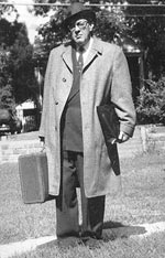 Black and white portrait of Howard Zahinser wearing a long coat and carrying a small suitcase and books. More about this picture plus a quote in the inset below.
